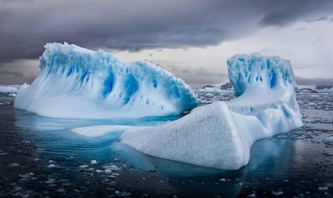 Zdjęcia lotnicze z gór lodowych na antarktydzie pod zachmurzonym niebem
