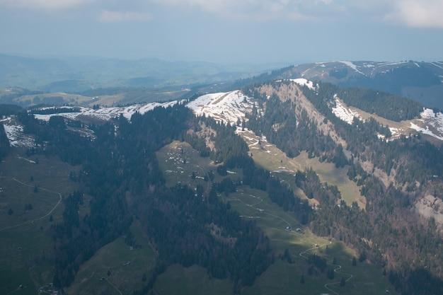 Zdjęcia lotnicze z pięknego pasma górskiego pokrytego śniegiem w pochmurne niebo