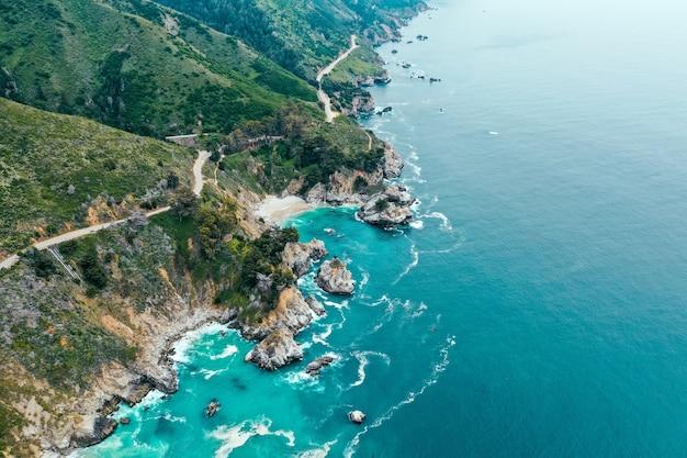 Zdjęcia lotnicze z pięknej linii brzegowej morza ze skałami i zieleni na plaży