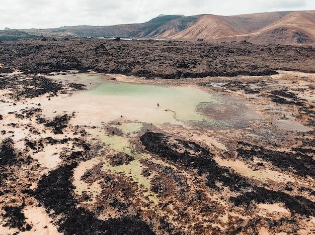 Zdjęcia lotnicze z pięknym błotnistym jeziorem tarn z dwiema osobami spacerującymi w nim