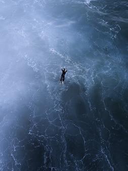 Zdjęcia lotnicze z pięknym krajobrazem i osobą pływającą w morzu w słońcu