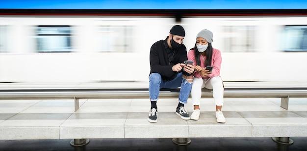 Zdjęcia panoramiczne. młoda międzyrasowa para kochanków w maskach i wełnianych czapkach siedzi na peronie metra