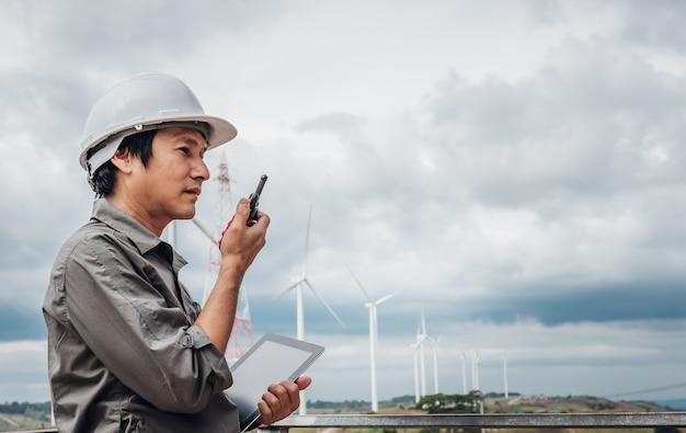 Zdjęcia portretowe azjatyckiego inżyniera, technika stojącego, trzymającego tablet i korzystającego z komunikacji radiowej, z turbinami wiatrowymi, dla ludzi i koncepcji produkcji energii elektrycznej.