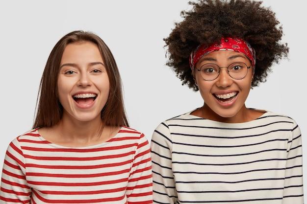 Zdjęcia uradowanych kobiet rasy mieszanej noszą swetry w paski, śmieją się z dobrego żartu z zadowolonymi minami, cieszą się swoim nowym spojrzeniem w lustrze, odizolowane na białej ścianie. zadowolenie