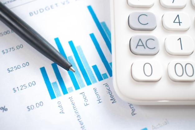 Zdjęcia z bliska długopisów, wykresów, finansów i kalkulatorów. na nowoczesnym białym stole.