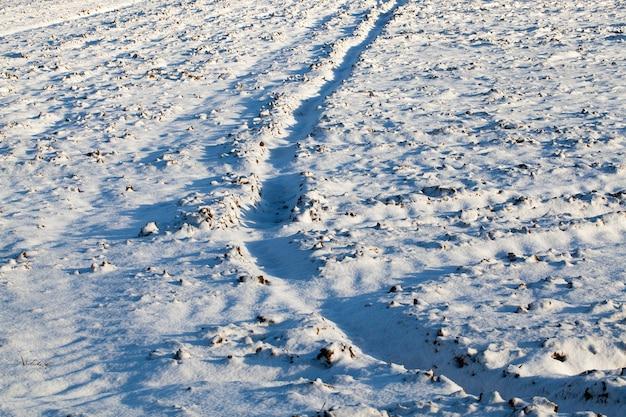 Zdjęcia ze zbliżeniami śladów opon pojazdów na śniegu