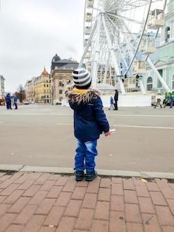 Zdjęcie 3-letniego chłopca patrzącego na wysoki diabelski młyn na ulicy miasta