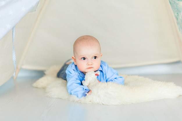 Zdjęcie adorable baby boyl na podłodze w swoim pokoju dziecinnym pod namiotem