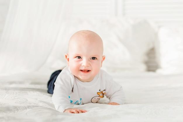Zdjęcie adorable chłopca leżącego na brzuchu i uśmiechnięte