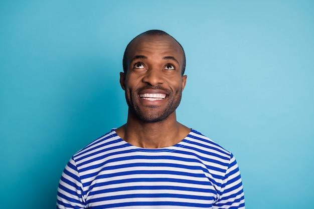 Zdjęcie afro-amerykańskiego faceta wygląda na copyspace promiennego uśmiechniętego na białym tle nad niebieskim kolorem tła