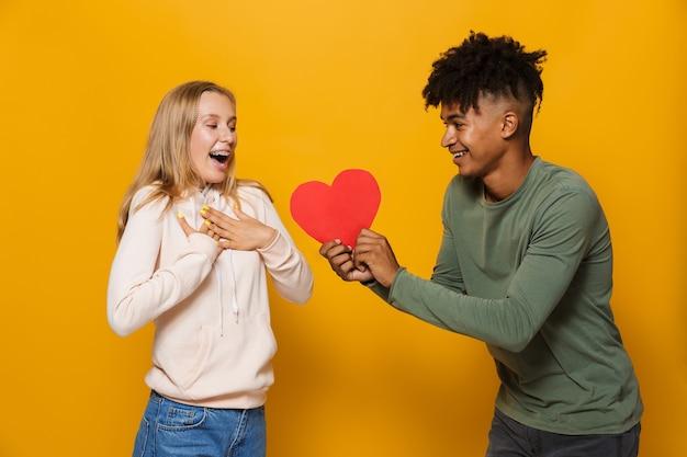 Zdjęcie afroamerykanina 16-18 lat dającego papierowe serce młodej kobiecie, odizolowanej na żółtym tle