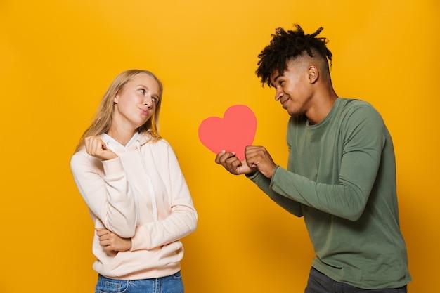 Zdjęcie afroamerykanina 16-18 lat dającego papierowe serce swojej dziewczynie, odizolowane na żółtym tle