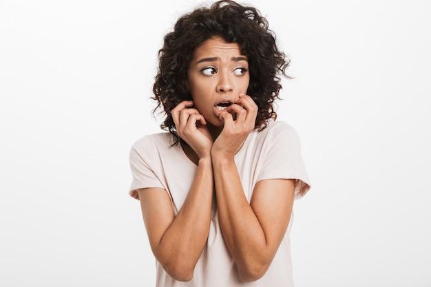 Zdjęcie amerykańskiej kobiety w wieku 20 lat w podstawowej koszulce obgryzającej paznokcie i czującej się niepewnie i przestraszonej, odizolowanej na białej ścianie
