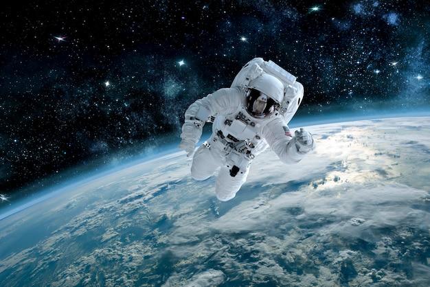 Zdjęcie astronautów w kosmosie, w tle planety ziemi. elementy tego zdjęcia zostały umeblowane