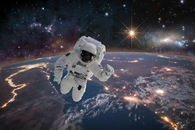 Zdjęcie astronauty w kosmosie. w tle planeta ziemia. elementy tego zdjęcia zostały umeblowane