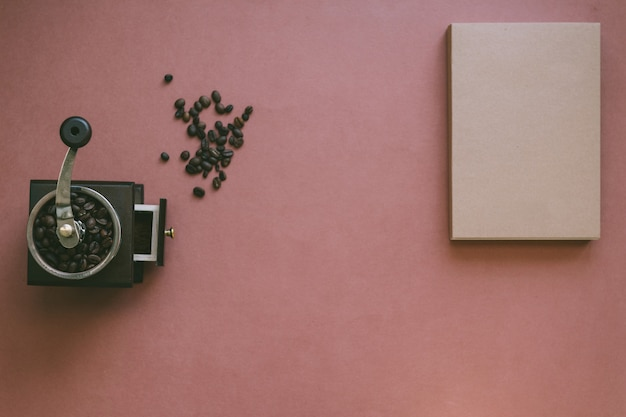 Zdjęcie atmosferyczne w stylu vintage i nastroju garści ziaren kawy leżących wraz z ręcznym drewnianym młynkiem do kawy w stylu retro i książką w starym stylu na brązowym teksturowanym tle