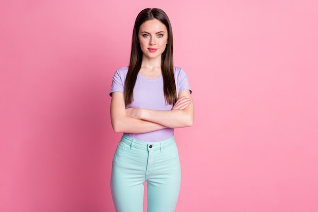 Zdjęcie atrakcyjne ładne ładne biznes dama dobry nastrój ramiona skrzyżowane pewny siebie apodyktyczny osoba szef nosić przypadkowy fioletowy t-shirt turkusowy spodnie na białym tle różowy pastelowy kolor tło