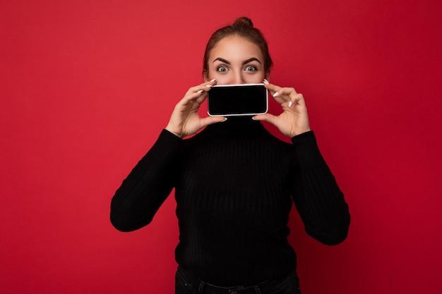 Zdjęcie atrakcyjne pozytywne młoda brunetka kobieta ubrana w czarny sweter stojący na białym tle nad czerwonym tle pokazując telefon komórkowy z pustym ekranem na makieta patrząc na kamery