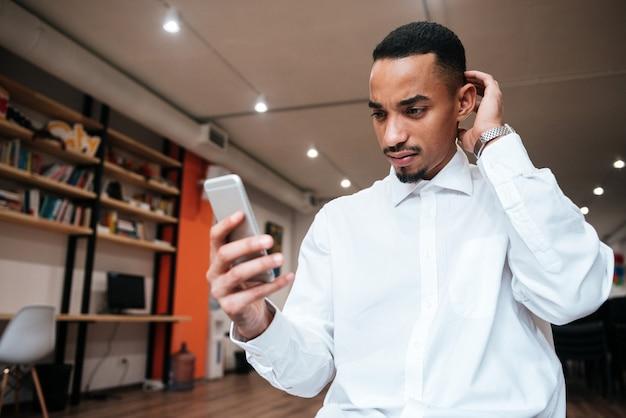 Zdjęcie atrakcyjnego biznesmena rozmawiającego przez telefon w biurze