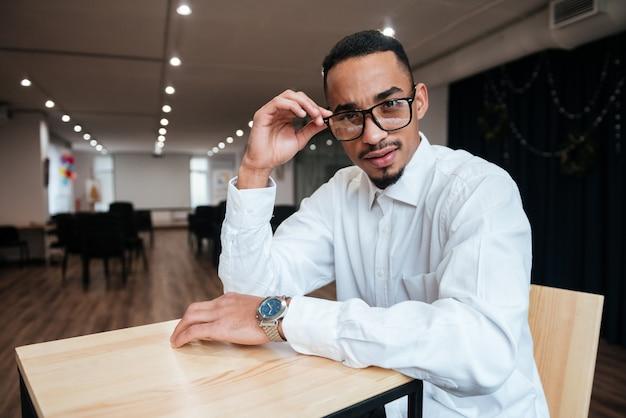 Zdjęcie atrakcyjnego biznesmena w okularach siedzącego przy stole i patrzącego na przód