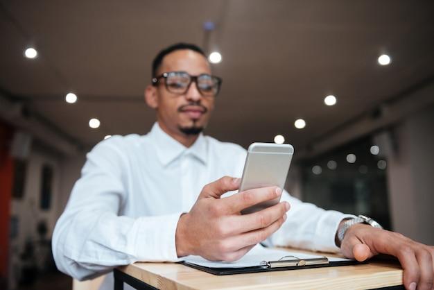 Zdjęcie atrakcyjnego biznesmena w okularach, siedzącego przy stole, rozmawiającego przez telefon