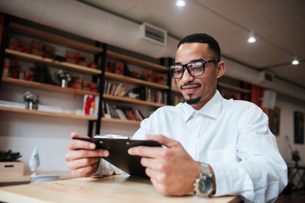 Zdjęcie atrakcyjnego biznesmena w okularach, siedzącego przy stole, trzymającego notatnik