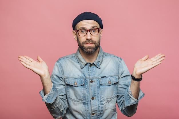 Zdjęcie atrakcyjnego brodatego mężczyzny nosi modne ubrania, ze zdumieniem wzrusza ramionami