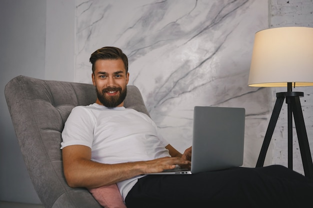 Zdjęcie atrakcyjnego faceta z gęstą brodą korzystającego z komunikacji online za pośrednictwem sieci społecznościowych, korzystającego z szybkiego łącza internetowego na laptopie, patrzącego na kamerę z pewnym siebie, zadowolonym uśmiechem