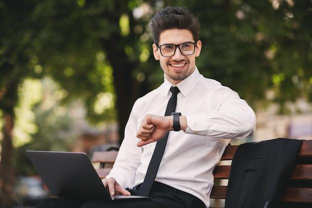 Zdjęcie atrakcyjnego mężczyzny w garniturze, pracującego na laptopie w zielonym parku i patrząc na zegarek