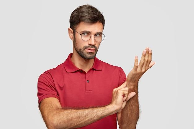 Zdjęcie atrakcyjnego mężczyzny w okrągłych okularach, trzyma rękę na nadgarstku