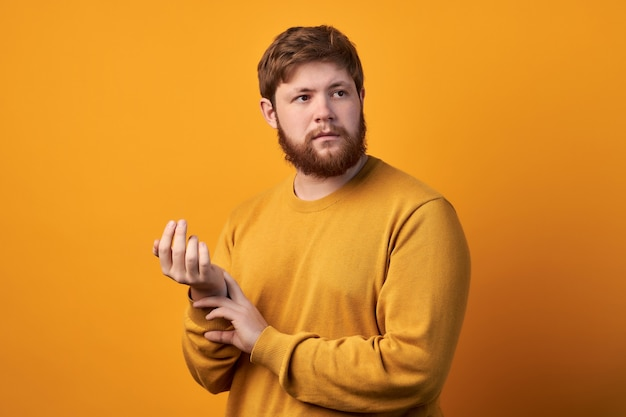Zdjęcie atrakcyjnego mężczyzny w okrągłych okularach, trzymającego rękę na nadgarstku, sprawdzającego puls lub tętno, dba o zdrowie, z kołataniem serca, modele na białym tle