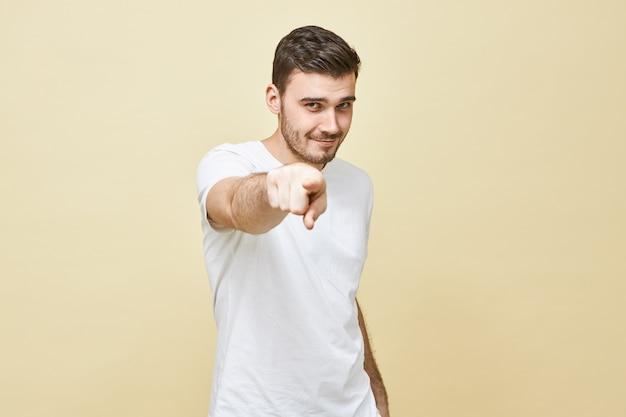 Zdjęcie atrakcyjnego, pewnego siebie, młodego bruneta w białej casualowej koszulce, patrząc prosto i wskazującym palcem wskazującym, dodającym pewności siebie, mając genialny pomysł. selektywna ostrość