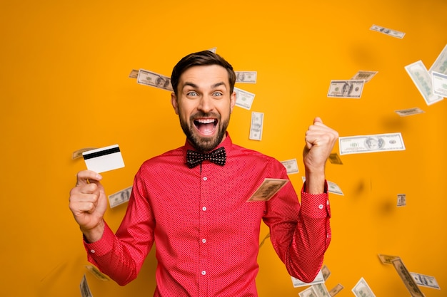 Zdjęcie atrakcyjnego zabawnego faceta trzymającego plastikową kartę kredytową bogata osoba pieniądze pieniądze spadają wszędzie krzycząc nosić modną czerwoną koszulę muszkę ubrania