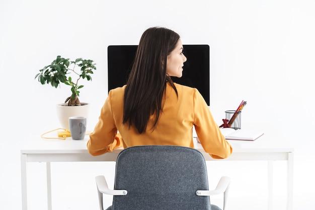 Zdjęcie atrakcyjnej brunetki 20-latki siedzącej przy stole i pracującej na dużym komputerze w jasnym biurze