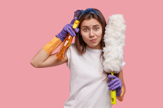 Zdjęcie atrakcyjnej gospodyni nosi opaskę na głowę i białą koszulkę, trzyma spray do prania i szczotkę do kurzu, nosi zwykłe ubrania, portmonetki usta
