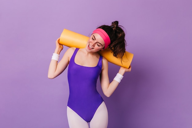Zdjęcie atrakcyjnej kobiety w stroju sportowym w stylu lat 80., pozująca z matą do aerobiku na fioletowej ścianie