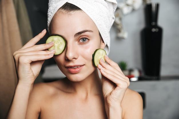 Zdjęcie atrakcyjnej kobiety z ręcznikiem na głowie trzymając plasterki ogórka na jej twarzy