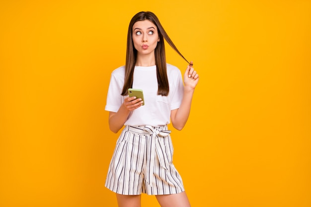 Zdjęcie atrakcyjnej ładnej damy trzymaj telefon spójrz w górę pusta przestrzeń rań zawinięty wokół palca wysyłaj nieśmiałe pocałunki noś biały t-shirt w paski szorty na białym tle żółty kolor ściana