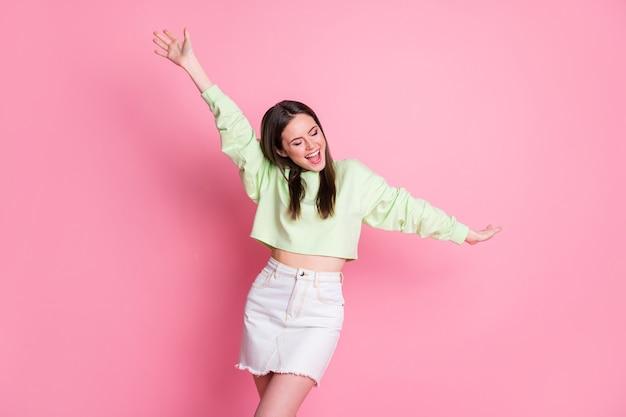 Zdjęcie atrakcyjnej ładnej milenijnej pani podnosić ramiona taniec dyskoteka impreza szczupła figura tancerz nosić przypadkowy zielony upraw sweter nagi brzuch dżinsy spódnica na białym tle różowy pastelowy kolor tło