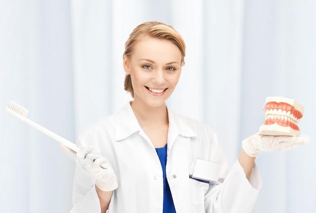 Zdjęcie atrakcyjnej lekarki ze szczoteczką do zębów i szczękami