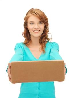 Zdjęcie atrakcyjnej nastolatki z kartonowym pudełkiem