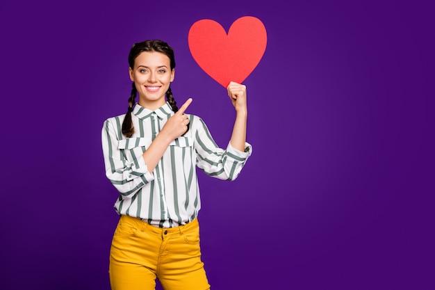 Zdjęcie atrakcyjnej pani trzymaj duże czerwone papierowe serce świętuje walentynki wskazać palec kreatywny pocztówka nosić koszulę w paski żółte spodnie na białym tle fioletowy kolor tło