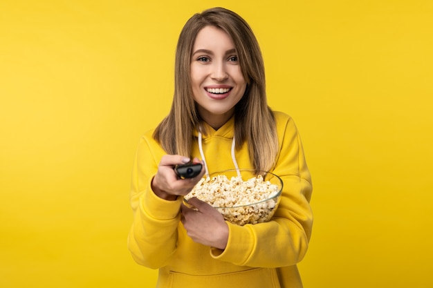 Zdjęcie atrakcyjnej pani trzymającej pilota od telewizora i talerz popcornu, z rozradowaną twarzą próbuje włączyć kanał. nosi dorywczo żółtą bluzę z kapturem, izolowane żółte tło.