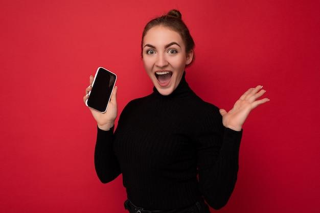 Zdjęcie atrakcyjnej, szczęśliwej, pozytywnej młodej brunetki ubranej w czarny sweter stojący na białym tle