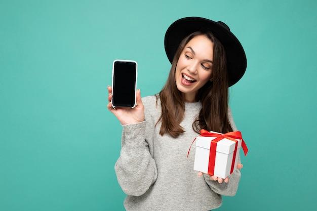 Zdjęcie atrakcyjnej szczęśliwej radosnej młodej brunetki osoby na białym tle na niebieskim tle ściany