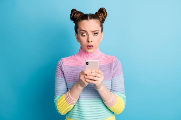 Zdjęcie atrakcyjnej zdziwionej zszokowanej nastolatki dwie bułki wpływowy freelancer przytrzymaj telefon czytaj zwolenników komentarze zły nastrój nosić pasiasty sweter na białym tle niebieski kolor tła