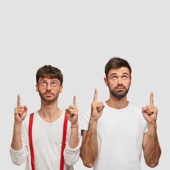 Zdjęcie atrakcyjnych dwóch brodatych młodych mężczyzn z poważnymi wyrazami twarzy, wskazujących oboma palcami wskazującymi do góry, pokazujące fajne miejsce do kopiowania, reklamujące coś na białej ścianie, ubranych w zwykłe ubrania