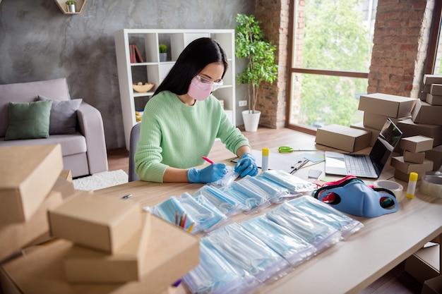 Zdjęcie azjatyckiej chińskiej damy ręce lateksowe rękawiczki biznes organizuj zamówienie twarz maski medyczne ręcznie robione pakiet umieść napisz adres klienta papierowa karta dostawa online sklep biuro domowe w pomieszczeniu