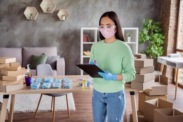 Zdjęcie azjatyckiej damy biznes zorganizowany zamówienia masek medycznych na twarz grypa paczki do dostarczania pudełek czeka obsługa pocztowa trzymaj schowek sprawdzanie informacji numery biuro domowe w pomieszczeniu