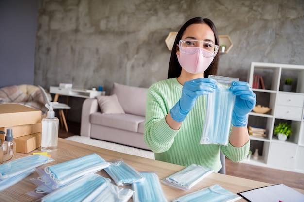 Zdjęcie azjatyckiej damy praca rodzinna firma organizuje zamówienia na twarz grypa maski medyczne pokazujące kamera internetowa proces przygotowywanie paczek pakiet dostawy bezpieczeństwo antywirusowe biuro domowe kwarantanna w pomieszczeniu